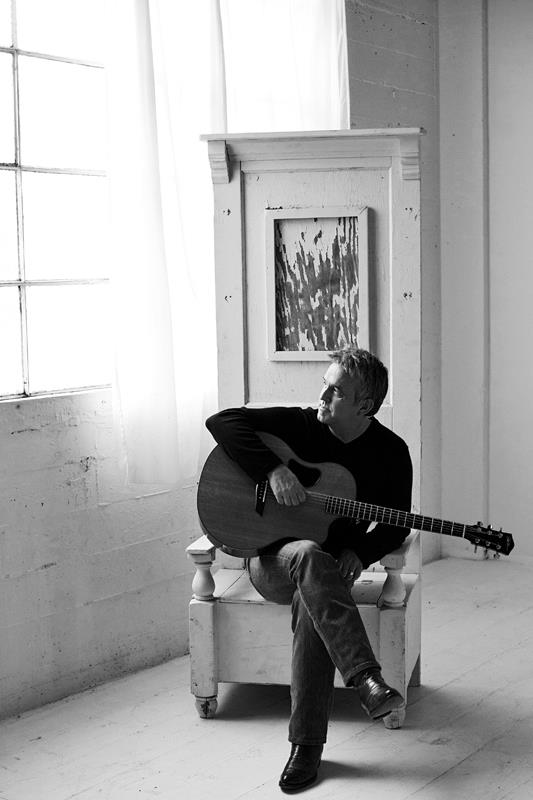 Wayne Watson sitting holding guitar in black and white